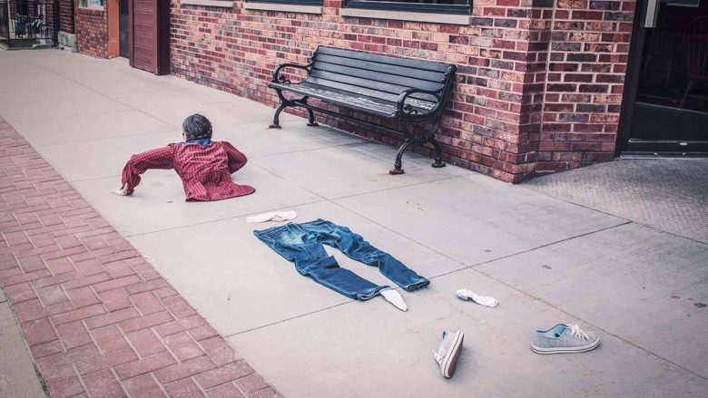A man trying to escape society, with his clothes scattered over the sidewalk