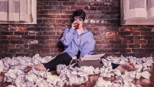 A woman on the floor, surrounded by paper because of writer's block