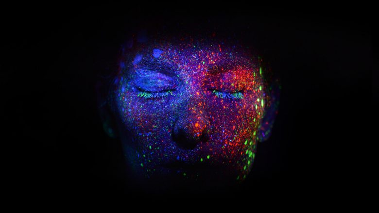 A colorful face on a dark background, glowing from purpose