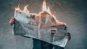 A guy reading a burning newspaper because he has FOMO